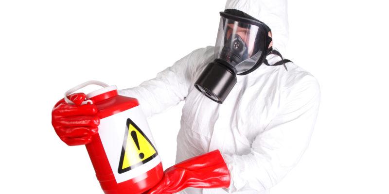 Applicateur en combinaison et masque qui tient avec des gants une bouteille toxique