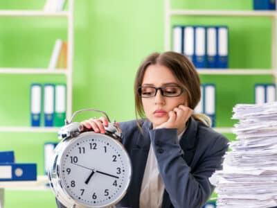 Jeune employée très occupée avec la paperasse en cours