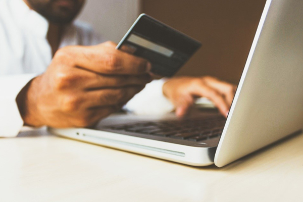Un clavier d'ordinateur, un homme avec une carte de crédit dans la main