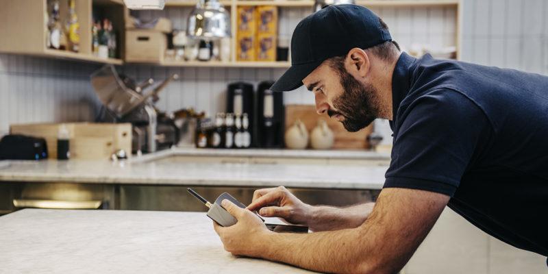 homme dans une cuisine appuyé sur une table