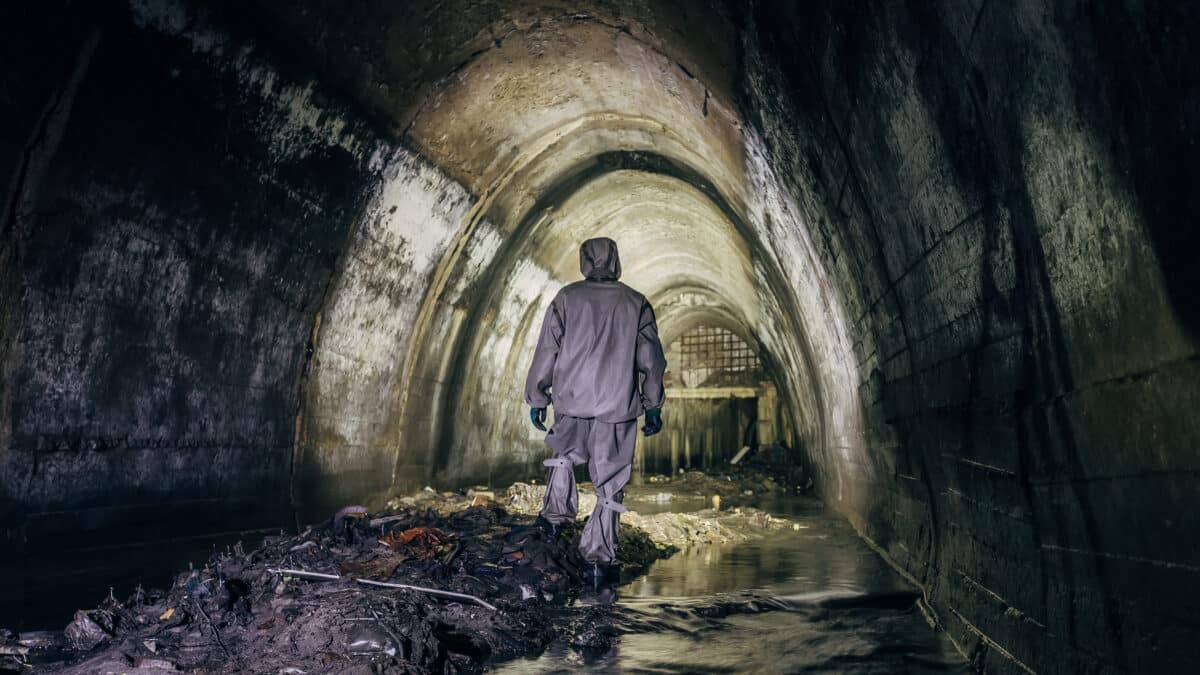 Travailleur en combinaison de protection chimique dans le tunnel d'égout souterrain