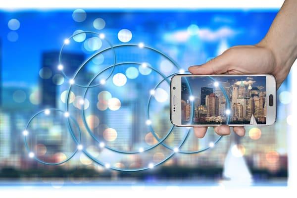 image contenant un smartphone tenu dans une main et des bâtiments dans le fond