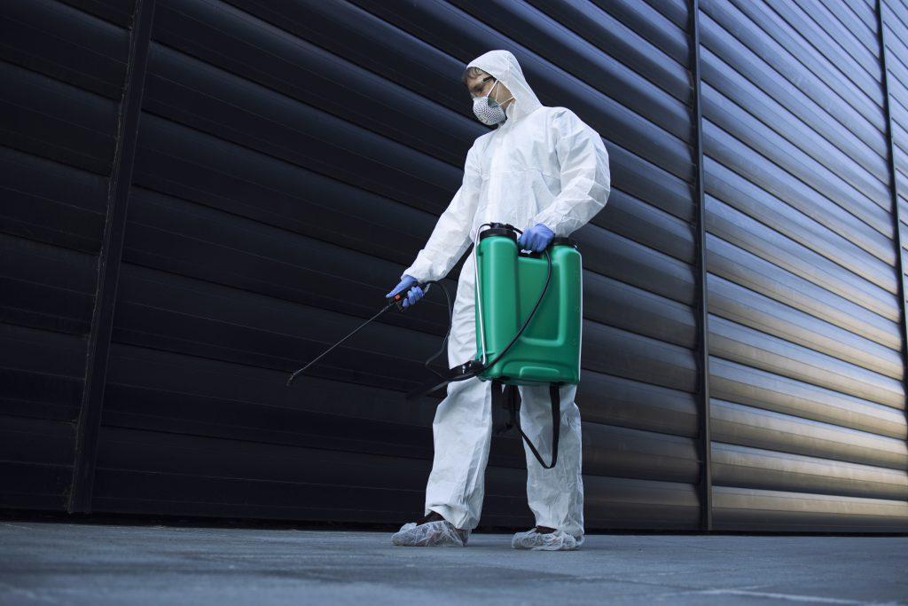 Un applicateur du secteur 3D détenant le certibiocide désinfecte une zone publique