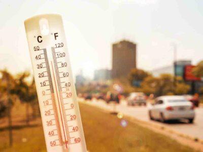 Thermomètre devant une scène urbaine pendant la canicule